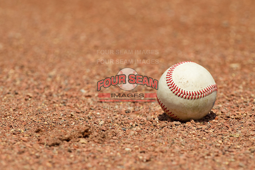 An International League baseball sits on the warning track behind home plate during the International League game between the Gwinnett Braves and the Charlotte Knights at Knights Stadium on July 28, 2013 in Fort Mill, South Carolina.  The Knights defeated the Braves 6-1.  (Brian Westerholt/Four Seam Images)