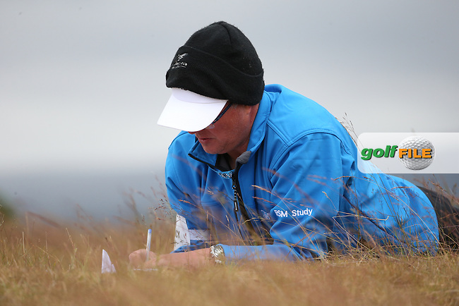 When the wind gets too much to complete the paperwork, lie down. RSM Player Efficiency Study volunteer hard at work  during Round Two of the 2016 Aberdeen Asset Management Scottish Open, played at Castle Stuart Golf Club, Inverness, Scotland. 08/07/2016. Picture: David Lloyd | Golffile.<br /> <br /> All photos usage must carry mandatory copyright credit (&copy; Golffile | David Lloyd)
