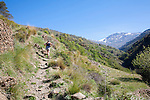 Woman hiker walking in the River Rio Poqueira gorge valley, High Alpujarras, Sierra Nevada, Granada Province, Spain