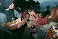 Sister Marie Christine Fabe hands out bags of powdered maise  to neighborhood children in Buranga, Rwanda, October 1994. The nun was helping AmeriCares with a clinic the New Canaan Connecticut humanitarian organization set up  on the road between Goma, Zaire (now Congo) and Kigali, Rwanda to help refugees returning from the camps in Goma and the people living in the area whose illnesses resulted from the destruction of what little infracstracture existed before civil war. (photo Rick D'Elia)