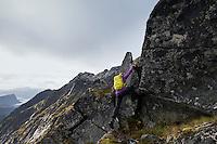Female hiker climb steep rocky ridge towards Østhimmeltind mountain peak, Vestvågøy, Lofoten Islands, Norway