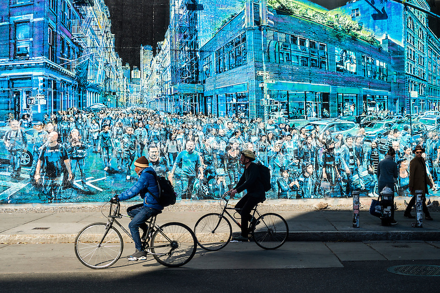 New York, NY - Cyclists and pedestriansin the East Village, pass a mural by Logan Hick,  entitled Story Of My Life, which features a crowd of people he photographed on the corner of Spring and Greene Street. ©Stacy Walsh Rosenstock
