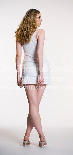 Caucasian blonde woman facing away from camera  holding handgun on white seamless