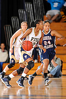 21 January 2012:  FIU guard Jerica Coley (22) handles the ball while being defended by FAU guard Teri Stamps (24) in the first half as the Florida Atlantic University Owls defeated the FIU Golden Panthers, 50-49, at the U.S. Century Bank Arena in Miami, Florida.