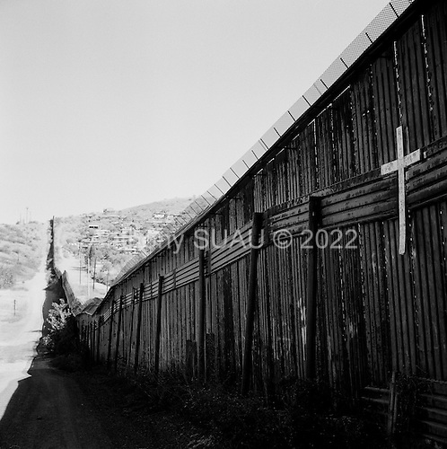 Nogales, Arizona.USA.October 20, 2006..A cross marks the death along the USA border fence as many illegals die trying to enter the county. The port of entry to the USA is near by. The city  is divided between Nogales Mexico and Nogales USA. The fence extends for several miles in either direction off the port of entry - then there is little to stop people from crossing illegally. Nogales is flooded with Mexicans legal and illegal and is mostly a transit and shopping town.