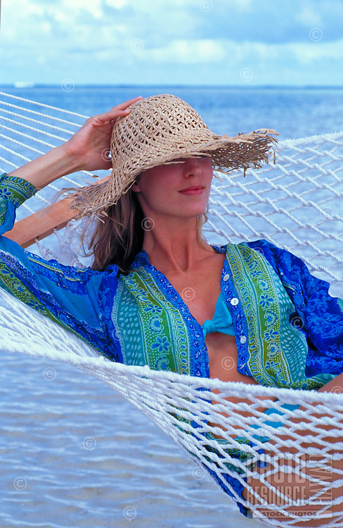 A woman with a large straw beach hat relaxes in a hammock at the beach.