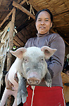 Reurn Reem holds a pig in the Cambodian village of Somrith. She is the leader of the Methodist women's group in the village, and received the pig as part of an income generating project sponsored by Methodist women.