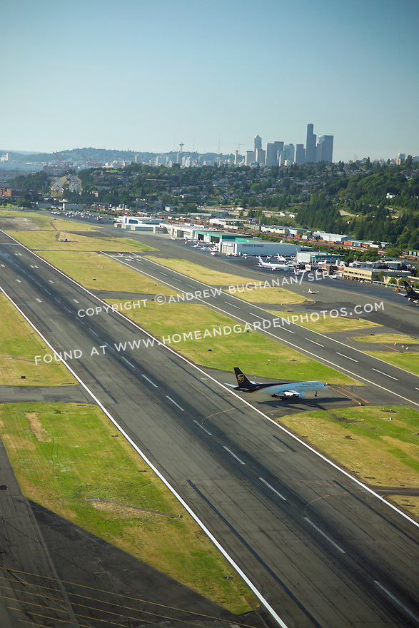 aerial view above Seattle's Boeing Field / King Co. International Airport, showing a UPS cargo plane turning off the runway in the late summer sunshine, while the buildings of downtown Seattle, and the Space needle, rise above the hills behind