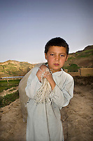 A boy carrying a sack at the edge of the village of Maghzar.