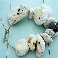 A wreath of seaside pebbles on floorboards painted a duck-egg blue