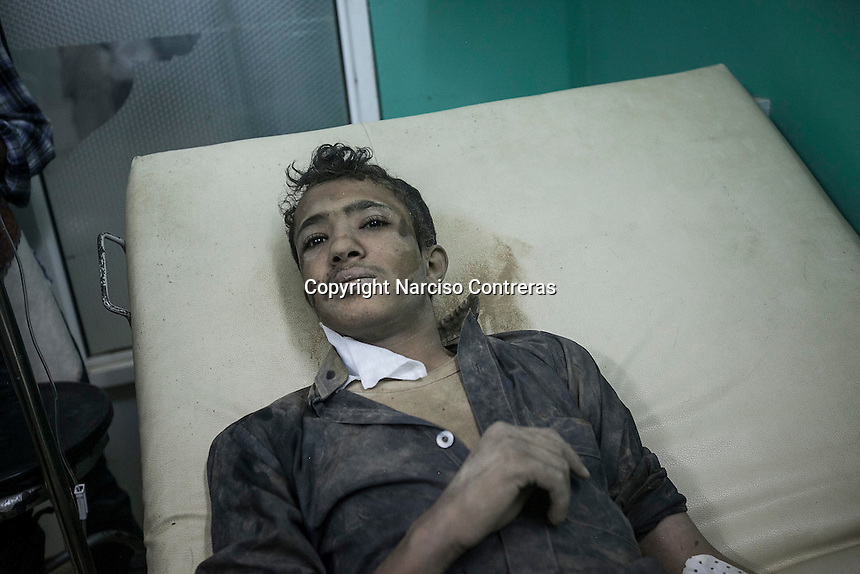 July 15, 2015 - Sa'dah, Yemen: Bashar Al Asadi, 14 years-old, lays in a trolley at the local hospital after he was rescued from the rubble of a house building hit by a fighter jet from the Saudi-led coalition in the northern city of Sa'dah, the stronghold of the Houthi movement in Yemen. The family of Bashar was buried under the rubble during the attack. Two members of his family, the mother and his brother (not pictured) died from their injuries, while his sister (not pictured) survived. (Photo/Narciso Contreras)
