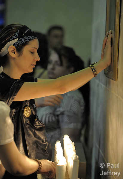 A woman prays with her hands on an icon following Mass in St. Raphael Chaldean Cathedral in Beirut, Lebanon.