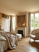 A traditional bedroom decorated in neutral tones with a wood floor. A mirror stands on the mantelpiece of a fireplace.