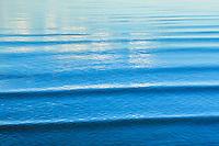Lugnt blått vatten men spegling av moln i Stockholms skärgård.