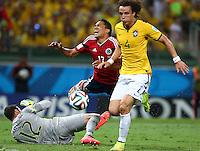 Carlos Bacca of Colombia is fouled by Brazil goalkeeper Julio Cesar for a penalty
