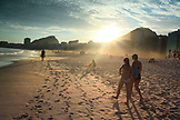 BRAZIL, Rio de Janiero, individuals walk down the sandy shoreline at Copacabana Beach