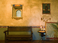Monterey County, CA<br /> Side chapel wall detail with bench and devotional candles in the Carmel Mission Basilica (1797) - Mission San Carlos Borromeo del Rio Carmelo