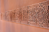 Carved stucco panel with decorative design and Arabic inscriptions on the wall of the Court of the Lions, built 1362 in the second reign of Muhammad V, in the Nasrid dynasty Palace of the Lions, Alhambra Palace, Granada, Andalusia, Southern Spain. The Alhambra was begun in the 11th century as a castle, and in the 13th and 14th centuries served as the royal palace of the Nasrid sultans. The huge complex contains the Alcazaba, Nasrid palaces, gardens and Generalife. Picture by Manuel Cohen