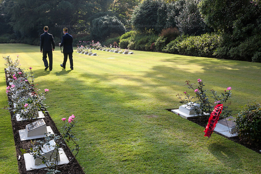 United States veterans walk between war graves after a Remembrance Day ceremony at the Yokohama War Cemetery, Hodogaya. Yokohama, Japan. Sunday November 9th 2014