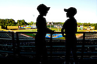 Two young fans are silhouetted against the field for the Charlotte Knights baseball team.
