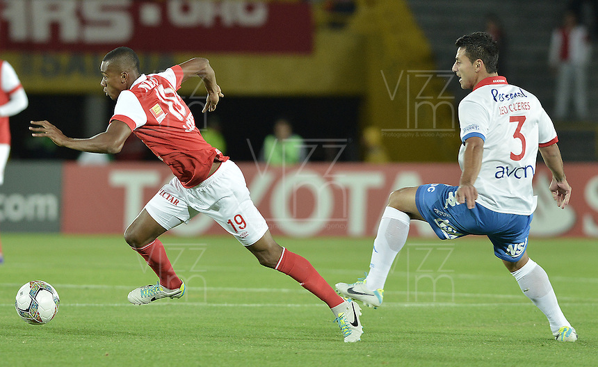 BOGOTÁ-COLOMBIA-11-02-2014. Jonathan Copete (Izq.) jugador del Independiente Santa Fe de Colombia, disputa el balón con Jose Leonardo Caceres (Der.) jugador del Nacional de Paraguay, durante partido entre Independiente Santa Fe y Nacional de la segunda fase, grupo 4, de la Copa Bridgestone Libertadores en el estadio Nemesio Camacho El Campin, de la ciudad de Bogota./ Jonathan Copete (L) player of Independiente Santa Fe of Colombia, vies for the ball with Jose Leonardo Caceres (R) player of Nacional of Paraguay, during a match between Independiente Santa Fe and Nacional for the second phase, group 4, of the Copa Bridgestone Libertadores in the Nemesio Camacho El Campin in Bogota city.  Photo: VizzorImage/ Gabriel Aponte /Staff