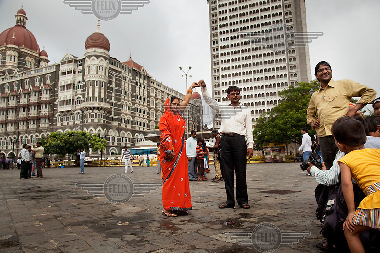 Tourists have their picture taken in front of the Taj Mahal Palace Hotel, the site of terrorist attacks in 2008. As the country's middle class grows, domestic tourism by Indians is booming.
