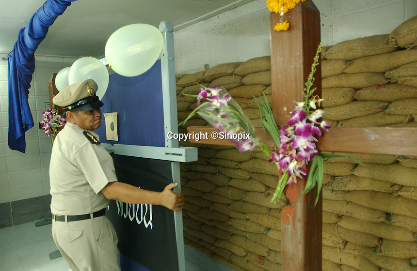 Thailand's only machine-gun executioner Chawalate Jarubun of Bangkwang Central prison stands in front of the wooden execution cross where has has personally executed 55 prisoners.