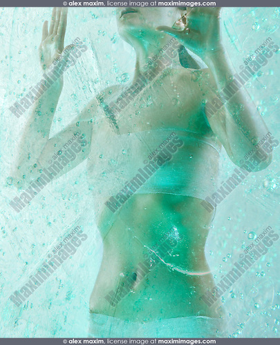 Beautiful young naked woman standing frozen in ice