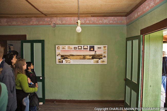 Visitors to the Trinity Atomic Bomb Test Site examine a panoramic photo of the MacDonald cabin while standing in the bedroom where the atomic test bomb was assembled during the famous trials in 1944 near Socorro, NM.