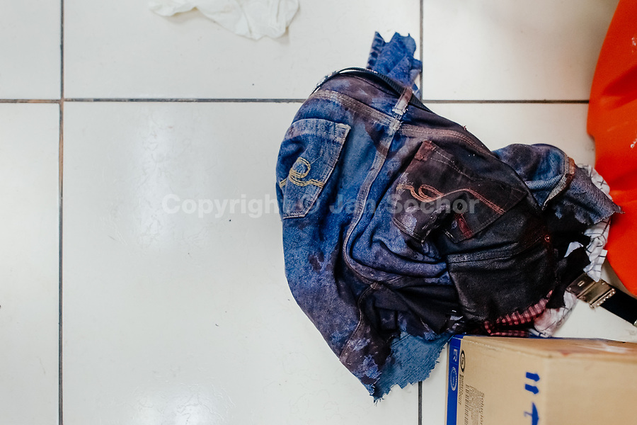Bloodied cut off jeans of a deadly injured gang member lie on the floor of the emergency department of a public hospital in San Salvador, El Salvador, 14 February 2015.