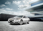One silver 2012 Chevrolet Malibu LS Sedan outdoors in courtyard of modern building.