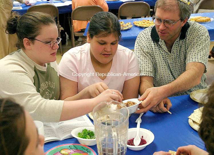 TORRINGTON, CT- 17 APRIL 2005-041705JS02--Brianna Wolfinger, 13 of Winsted, left, Stephanie Abramo, 13 of Torrington, center, and Ron Beilstein of Harwinton sample bitter roots with haroseth, a mixture of chopped walnuts, wine, cinnamon and apples that represents the mortar the Jewish slaves used to assemble the Pharaoh's bricks, during a model Passover Seder Sunday at the Beth El Synagogue in Torrington. The event was sponsored by the Interfaith Council of Northwest Connecticut --- Jim Shannon Photo--Interfaith Council of Northwest Connecticut; Passover; Seder; Brianna Wolfinger; Winsted; Stephanie Abramo; Ron Beilstein; Harwinton are CQ