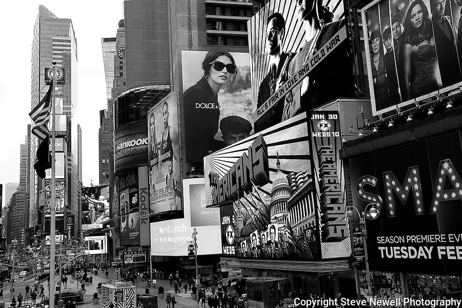 """Americans"" Black and White Times Square Manhattan New York. Times Square is like a little city all to itself that provides plenty of entertainment, bars, restaurants, shopping and attractions for everyone.  You can't possibly do and see it all in a one week vacation. I went to two Broadway plays and one off broadway play while I was staying in Manhattan for eight days shooting photography.  The local employees recommended their favorite restaurants and bars in the area that were excellent and affordable.  Times Square has so much to offer everyone from all walks of life will be satisfied on a visit to the must see district. I made several trips to the area spanning morning noon and night- to late night. When the huge storm blew into New York on the weekend I found myself in the middle of Times Square alone enjoying the light snow fall.  A memory I will cherish!"