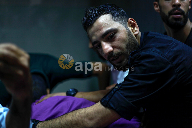 Relatives of a Palestinian gunman who was shot dead by Israeli security forces, react at Indonesian hospital in the northern Gaza Strip August 18, 2019. Israeli forces last night killed three Palestinians and injured a fourth one in an artillery attack near the town of Beit Lahia, north of the Gaza Strip, according to the Ministry of Health. Photo by Ramez Haboub