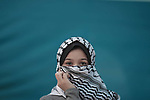 A girl wearing Palestinian traditional checkered keffiyeh against green backgraound. Photo by Sanad Ltefa