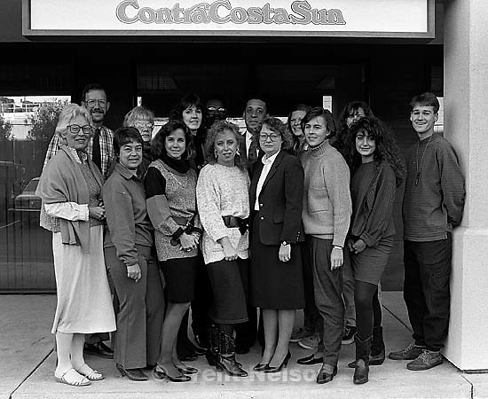 Contra Costa Sun staff photo. Front row: Dorothy Bowen, ? ? (talkative typist), Kate Sheridan, Cindy Coles, Cathy Tallan, Sandra Harris, ? ?, Trent Nelson. Back row: Jim Grodnik, Diane Overly, Jane ?, ? ?, Craig Johnson, Jane ?, Paula ?<br />