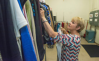 NWA Democrat-Gazette/BEN GOFF @NWABENGOFF<br /> Gwen Shankle of Springdale, who volunteers as a image consultant, sorts donated clothes Saturday, Aug. 4, 2018, during a 'Suit Sorting Saturday' at Dress for Success Northwest Arkansas in Frisco Station Mall in Rogers. Dress for Success, with an additional boutique in Springdale, helps empower women entering the workforce by providing support, classes and appropriate professional attire free of charge. Their clients are referred to them from other area organizations, and include women trying to overcome poverty, new citizens and those returning to society after being incarcerated. Volunteers gather once a month at the Rogers location for a Suit Sorting Saturday to help with intake, sorting, cleaning and repair of donated clothing. The organization plans to hold their annual inventory reduction sale Aug. 25., which is open to the general public and helps fund the organization.