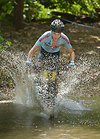 NWA Democrat-Gazette/BEN GOFF @NWABENGOFF<br /> Benn Stover, a category 1 men age 15-49 racer from Lawrence, Kan., fords a creek Sunday, July 16, 2017, during cross country races on the final day of the 19th annual Fat Tire Festival at Lake Leatherwood City Park in Eureka Springs.