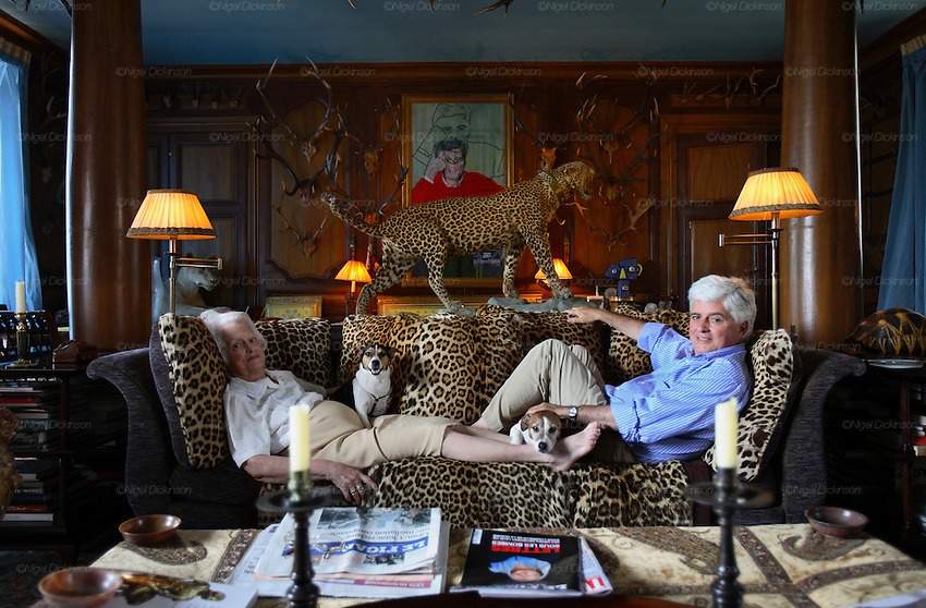 """France's ostentatious interior decorator and landscape architect, self-made man Jacques Garcia in his Norman country retreat 'le Chateau du Champ de la Bataille. He is responsible for the Parisian Ladurée teahouse and Hotel  Costes. His client list includes the Sultan of Brunei. He bought the chateau, one hours drive from Paris, at le Neubourg in Normandie, twenty years ago and faced with one of the great masterpieces of French Architecture, his self appointed task was to make it more sublime. Hardly touching the facade, he re-designed the interiors to be lavish interpretations of Baroque, recalling Louis XIV and Marie Antoinette. The stylish gardens contain Roma style temples, an amphitheatre and fountains.  The chateau, open to the public, attracts 30,000 visitors per year. In 2007, with the addition of  restaurant and hotel rooms, the project will be finished.///Chateau du Champ de la Bataille interior: Jacques Garcia with his 84 year old mother """"Jeanne Garcia"""", with his dog """"Leon"""" and is mother's """"Olymph"""" - Leon's fiancée in the Hunting Lounge """"Salon Chasse""""."""