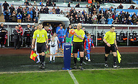 Referee Mike Dean (C) picks up the match ball before the Barclays Premier League match between Swansea City and Crystal Palace at the Liberty Stadium, Swansea on February 06 2016