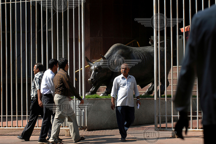 Investors and members of the public pass the statue of bronze bull at the fortified entrance to the Stock Exchange.