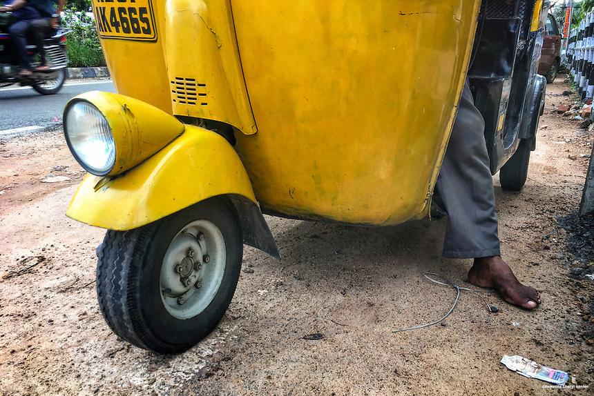 A barefoot auto rickshaw driver waits for a fare in Thiruvananthapuram, Kerala, India  June 5, 2017 (Cellphone Photo by Cheryl Senter)