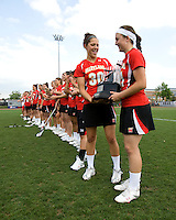 Brittany Poist (27) and Danielle Kirk (30) hold the conference trophy after the ACC women's lacrosse tournament finals in College Park, MD.  Maryland defeated North Carolina, 10-5.