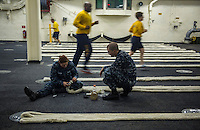 130425-N-DR144-382 Pacific Ocean (April 23, 2013)- Boatswain's Mate 2nd Class Casey Crossley instructs Boatswain's Mate Seaman Nicole Harman as she whips the ends of mooring lines while other Sailors jog in the upper vehicle stowage deck aboard the amphibious transport dock ship USS Anchorage (LPD 23). Anchorage is currently en route to its namesake city of Anchorage, Alaska for its commissioning ceremony May 4. (U.S. Navy photo by Mass Communication Specialist 1st Class James R. Evans / RELEASED)