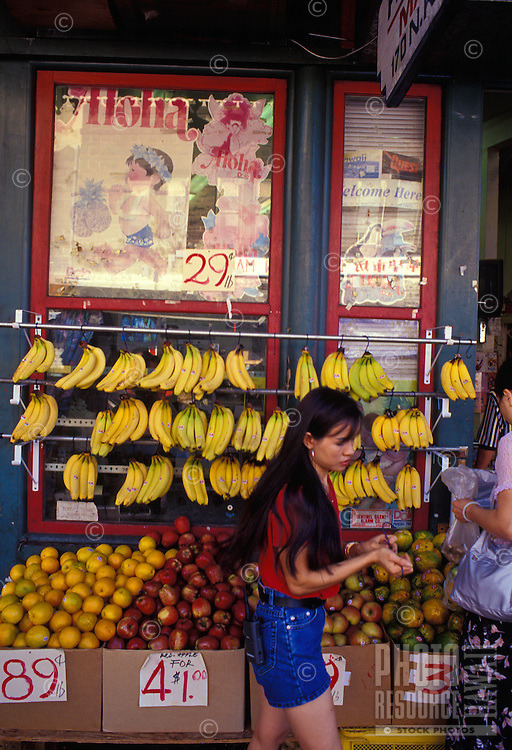 Woman shopping for fruits and vegetables at a Chinatown food market near King and Mauna Kea Streets in Honolulu