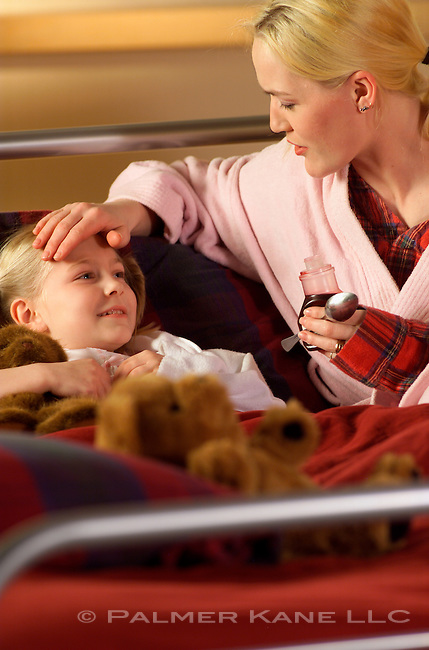 Mother administering cough medicine to sick daughter confined to bed