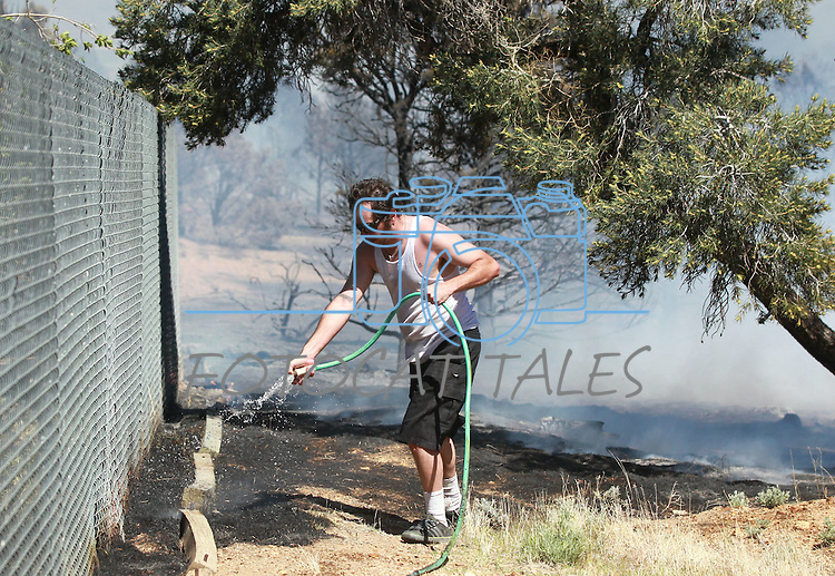 A resident tries to put out hot spots while firefighters battle a wind-driven fire that has destroyed at least two homes and a number of outbuildings in Topaz Ranch Estates, south of Gardnerville, Nev., on Tuesday, May 22, 2012. (AP Photo/Cathleen Allison)