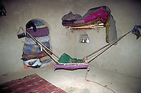 Inside afghan house with baby hammock
