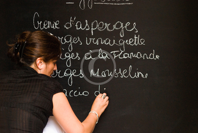 Belgium, Brussels, Woman writing menu on chalk board