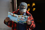 A man reads the glossy funeral program for Tyshawn Lee, 9, who was shot multiple times while playing basketball in an alley on November 2, 2015, in the entrance of St. Sabina's in Chicago, Illinois on November 10, 2015. Police allege the killing was a retaliatory gang hit which would mark a new turn in Chicago's gang wars.
